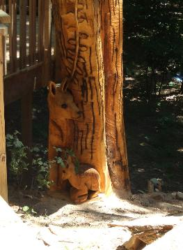 Doe and fawn chainsaw carvings in tree stump
