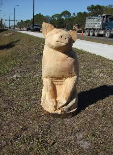Sitting Pig chainsaw carving